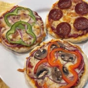 Three mini pizzas with various toppings on a white plate