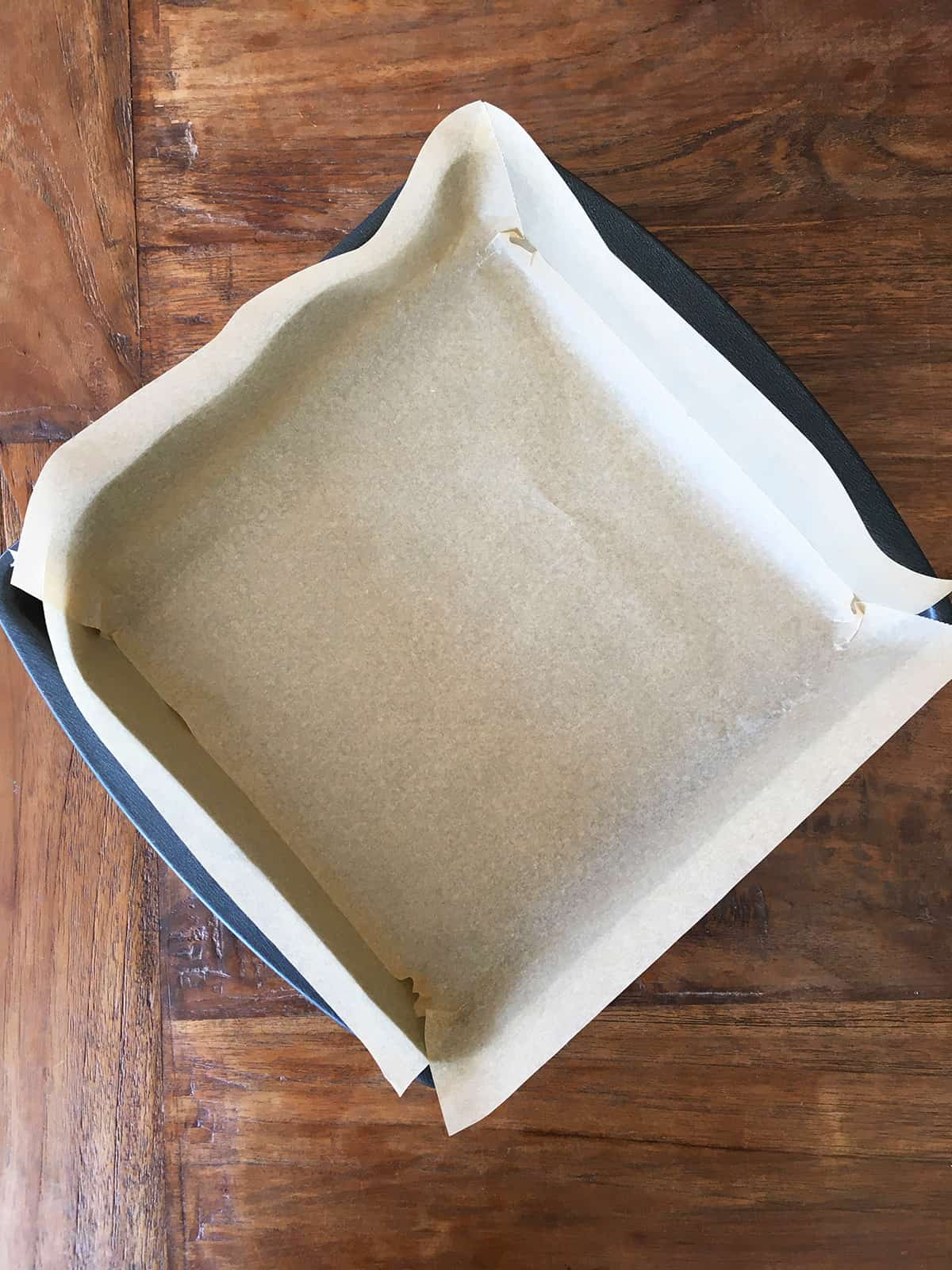 Square metal pan lined with parchment paper on a brown wood table