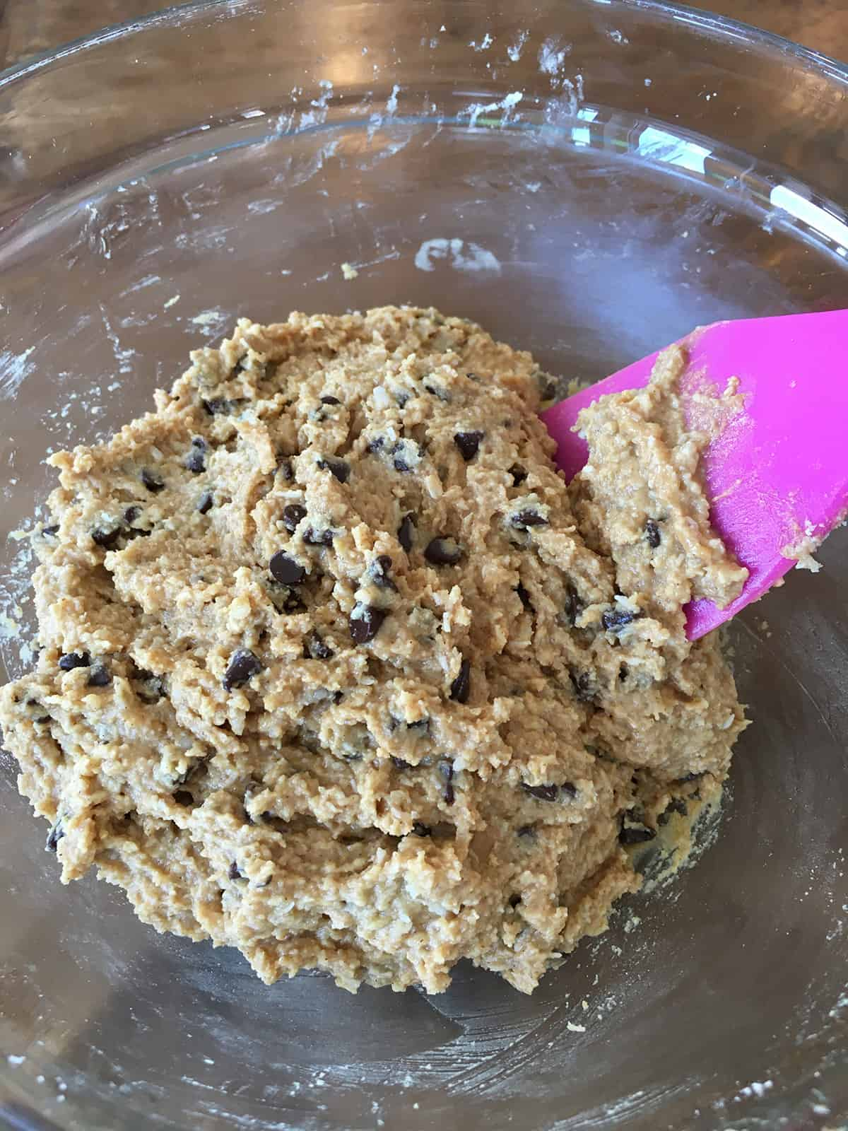 Protein ball batter with chocolate chips in a glass bowl with a purple silicone spatula