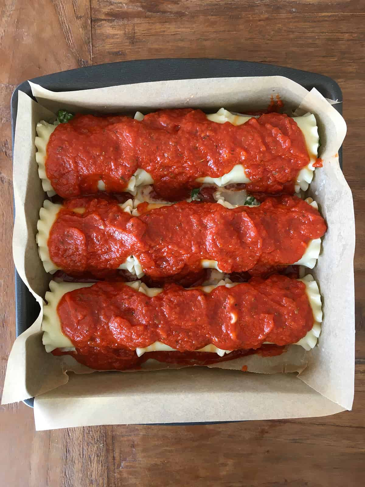 Lasagna roll ups topped with marinara sauce in a parchment paper-lined pan