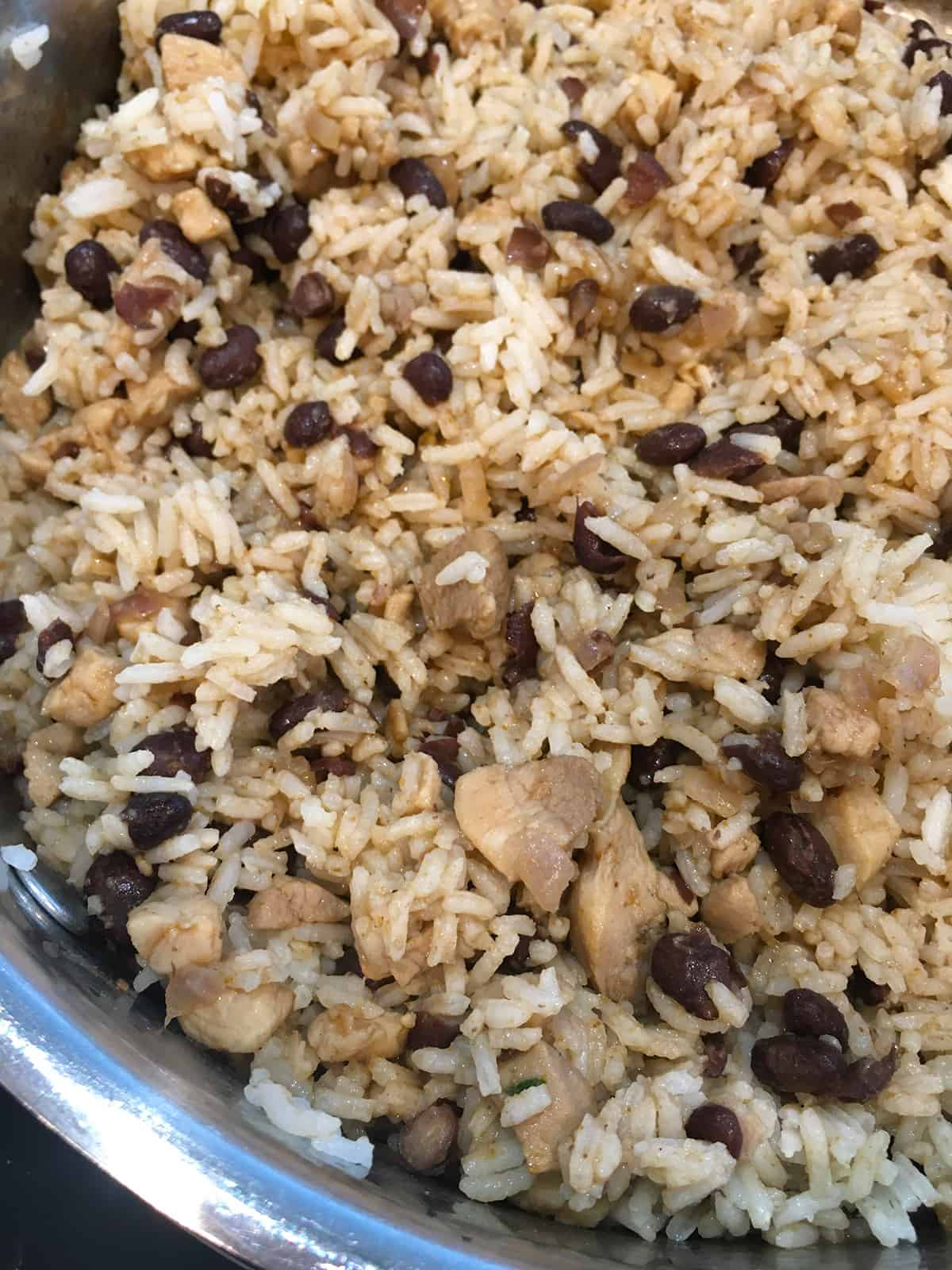 Close up of chicken burrito filling with rice and black beans in stainless steel pot