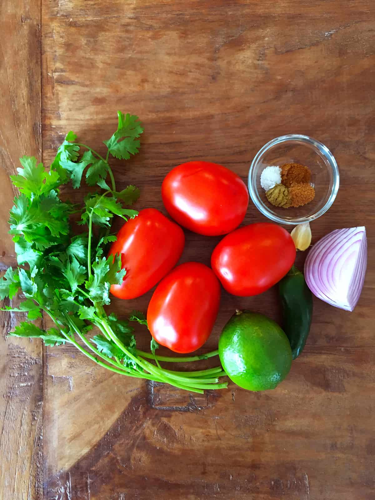 Cilantro, Roma tomatoes, lime, jalapeño, garlic, red onion and spices for homemade salsa