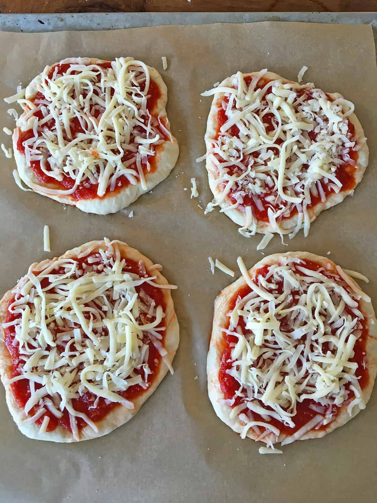 Four mini cheese pizzas assembled on a baking sheet lined with parchment paper