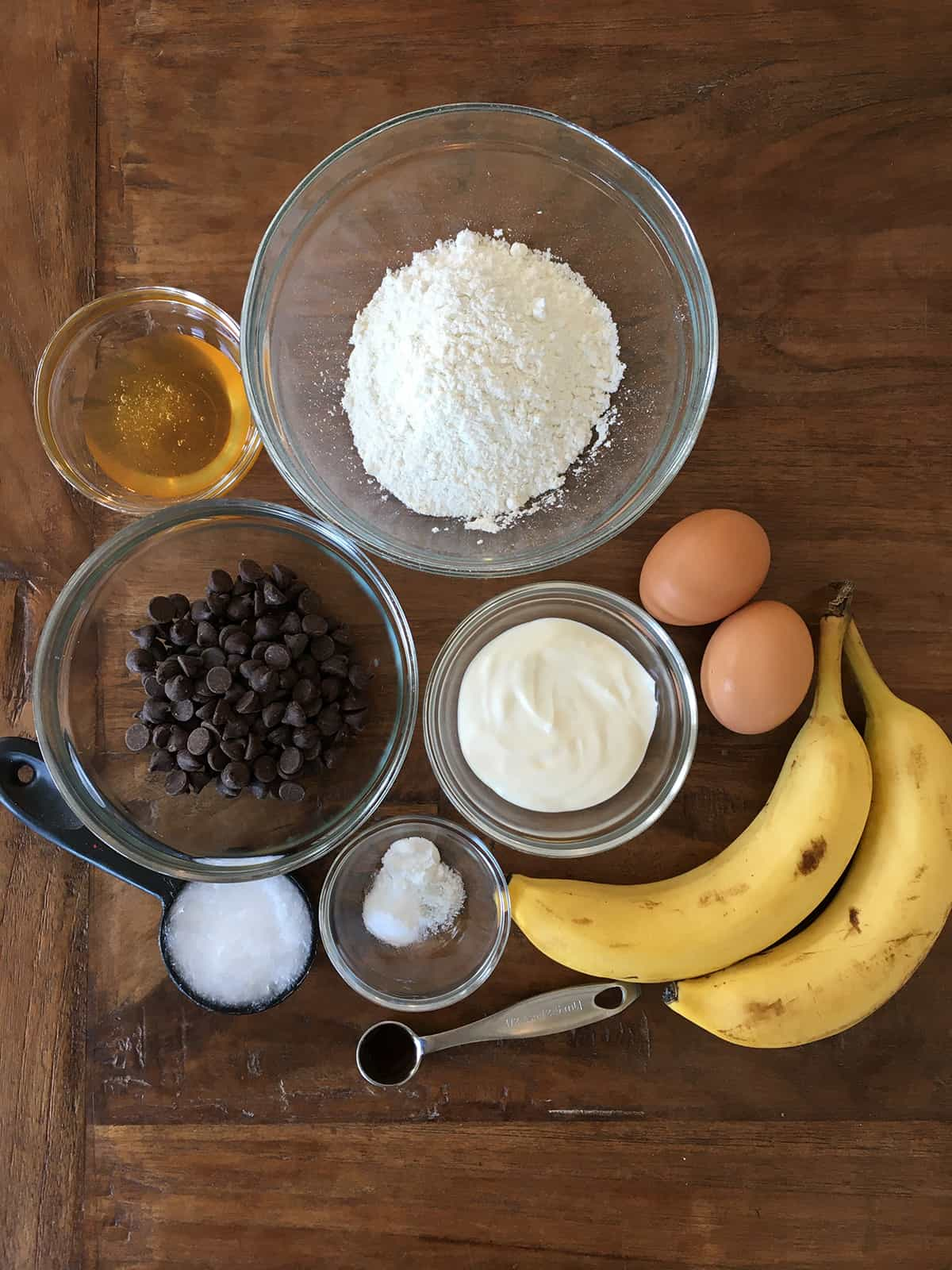 Banana chocolate chip muffin ingredients, some in glass meal prep bowls, on a brown wood table