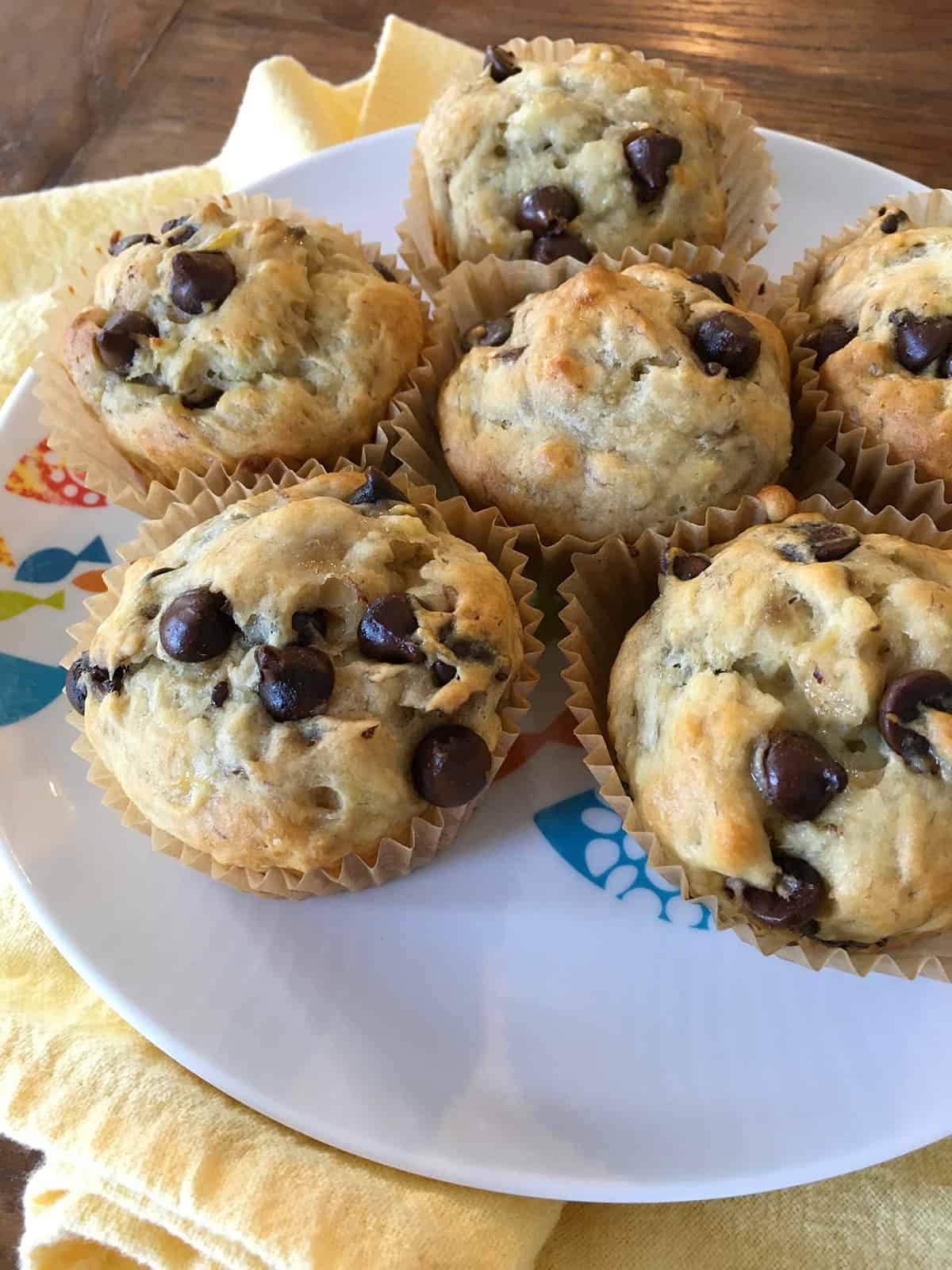 Six banana chocolate chip muffins in paper liners on a kids plate