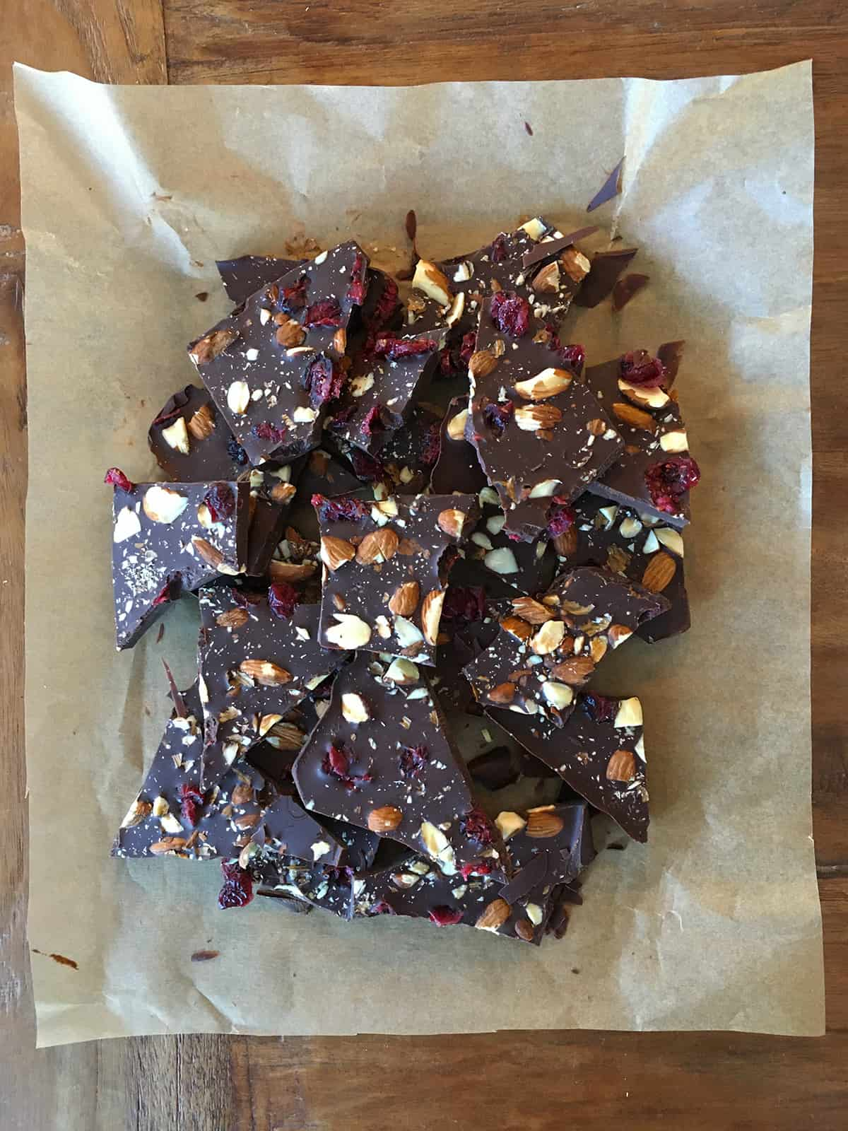 Chocolate bark with almonds, dried cranberries and sea salt on parchment paper