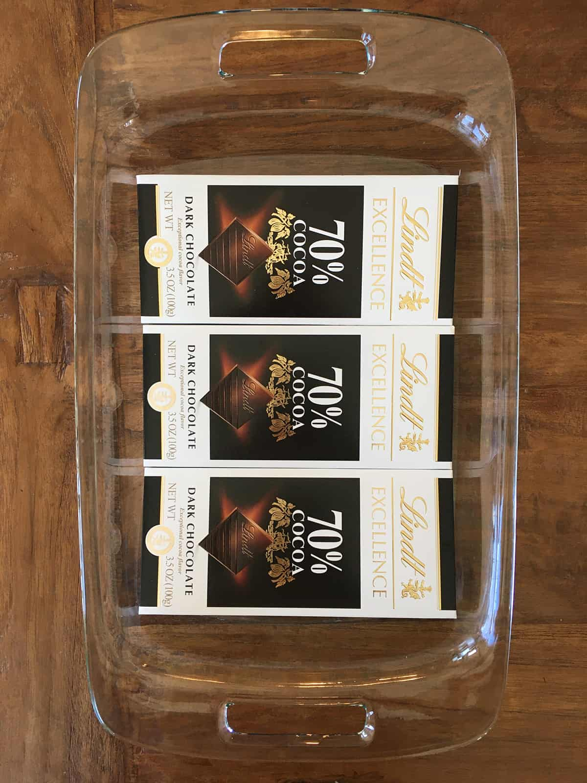 Three dark chocolate bars in a glass baking dish on a brown wood table
