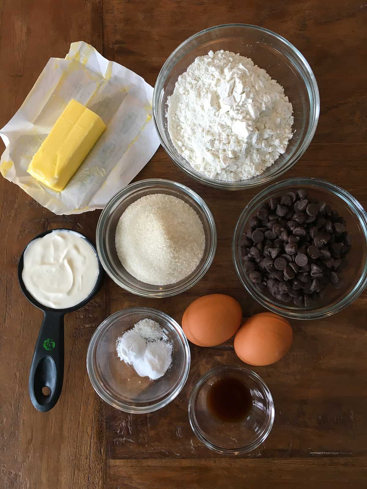 Chocolate chip muffin ingredients, some in glass meal prep bowls, on a brown wood table