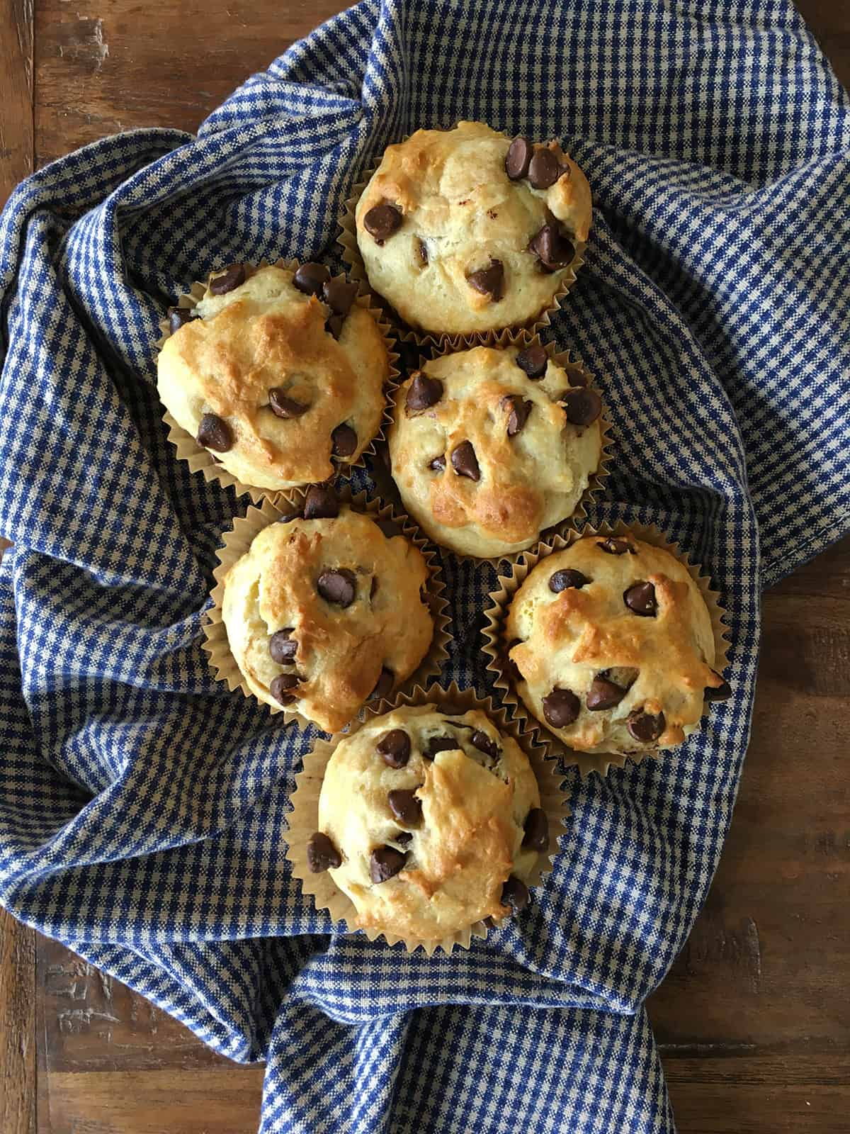 Chocolate chip muffins on a blue and tan plaid napkin atop a brown wood table