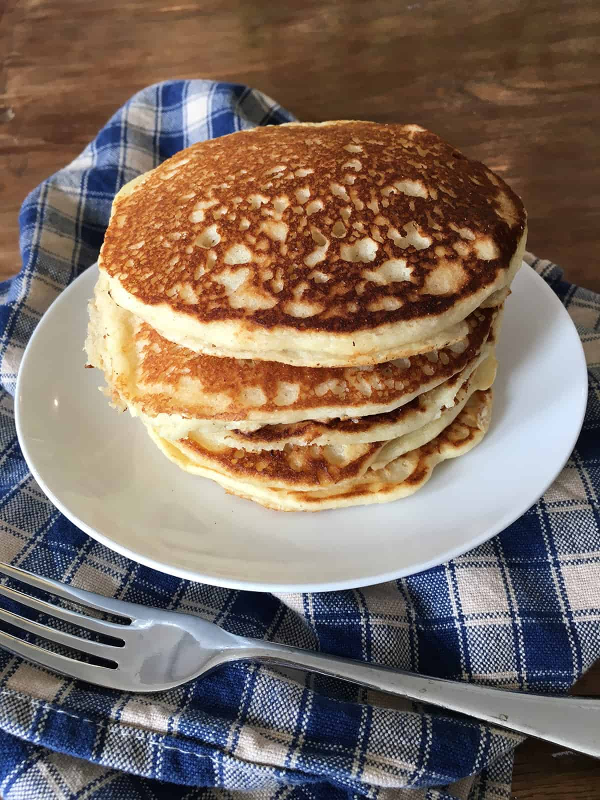 Stack of gluten free pancakes on a white plate with a blue and tan plaid napkin