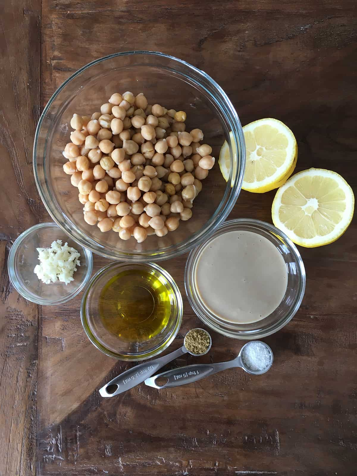 Chickpeas, lemon halves, spices and other hummus ingredients in glass food prep bowls on a brown wood table
