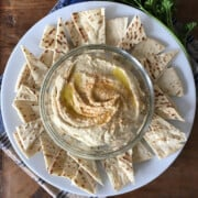 Homemade hummus in a glass bowl with pita wedges