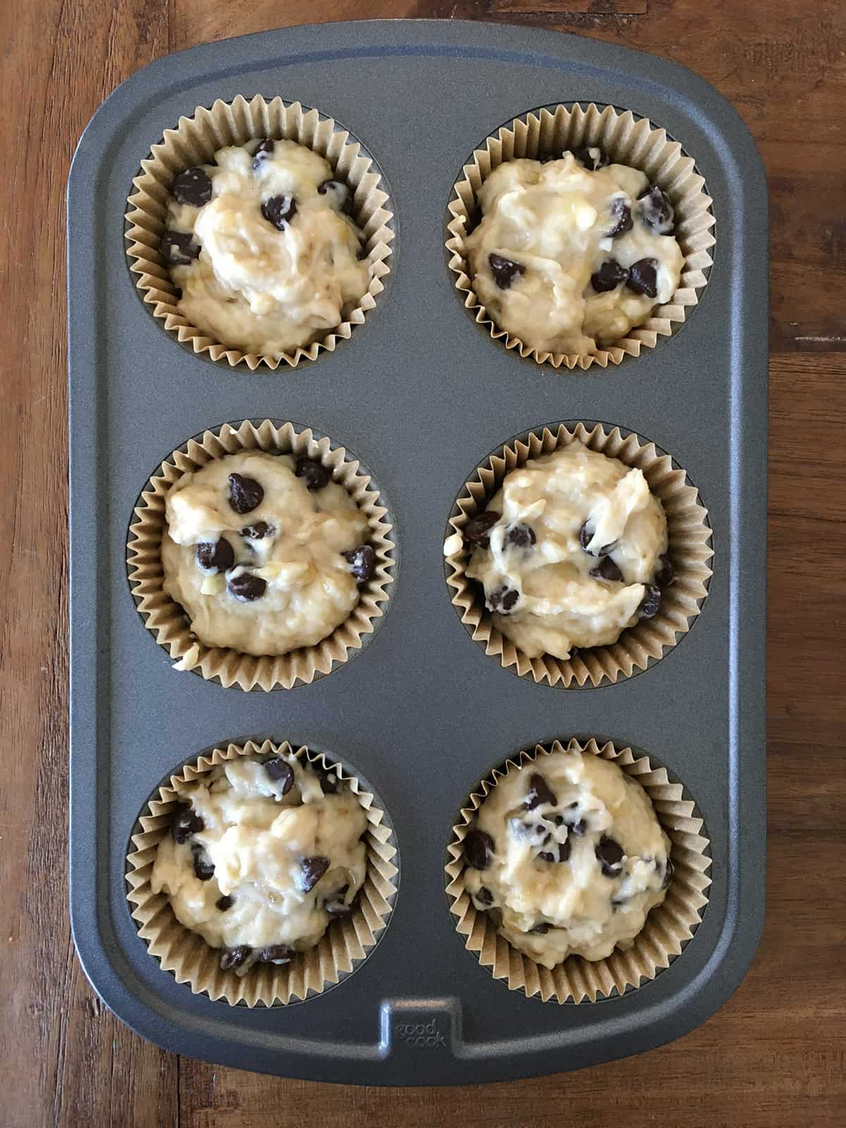 Six-muffin tin lined and filled with banana chocolate chip muffin batter