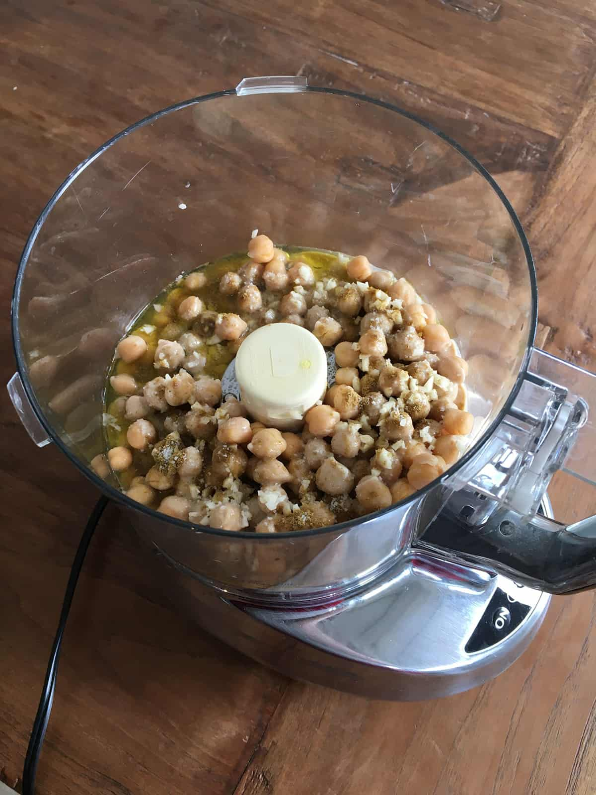 Chickpeas, garlic and other hummus ingredients in a food processor on a brown wood table