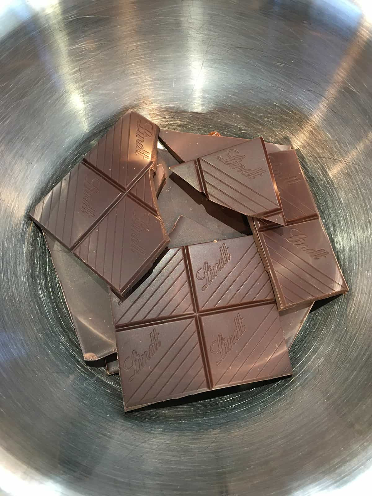 Pieces of dark chocolate bars in a stainless steel mixing bowl