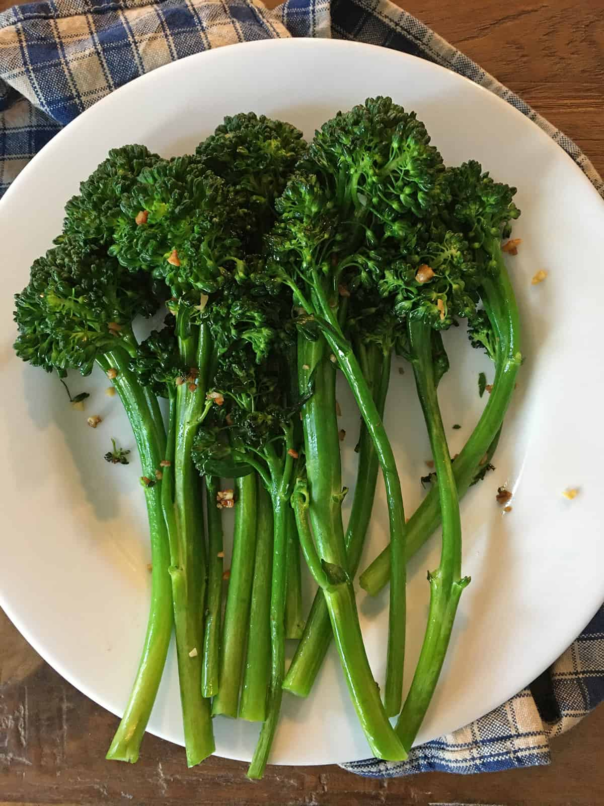 Sautéed broccolini with garlic on a white plate atop a blue and tan plaid napkin
