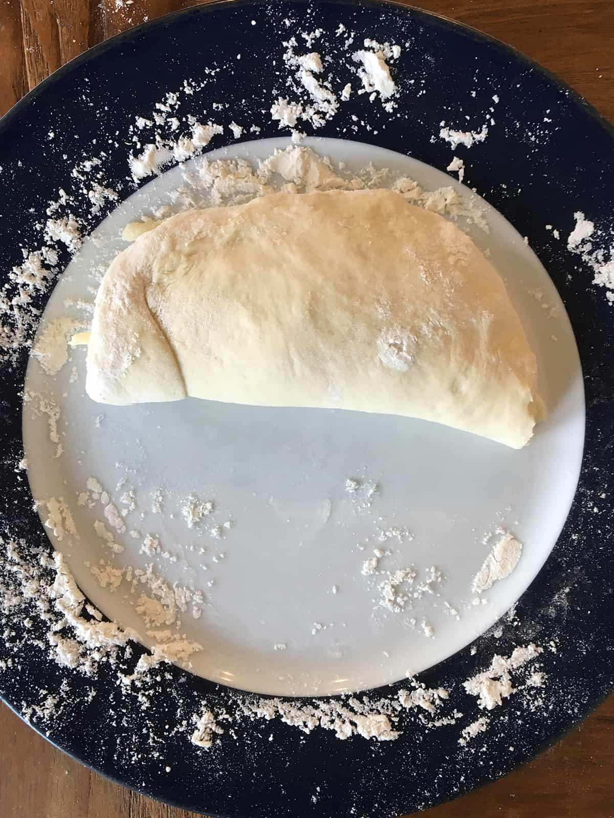 Calzone dough folded over the filings on a blue and white plate
