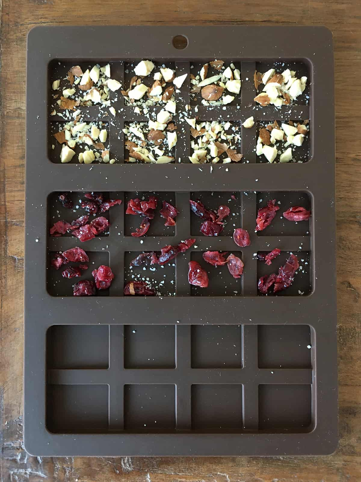 Chocolate bar mold partially filled with chopped almonds, dried cranberries and sea salt