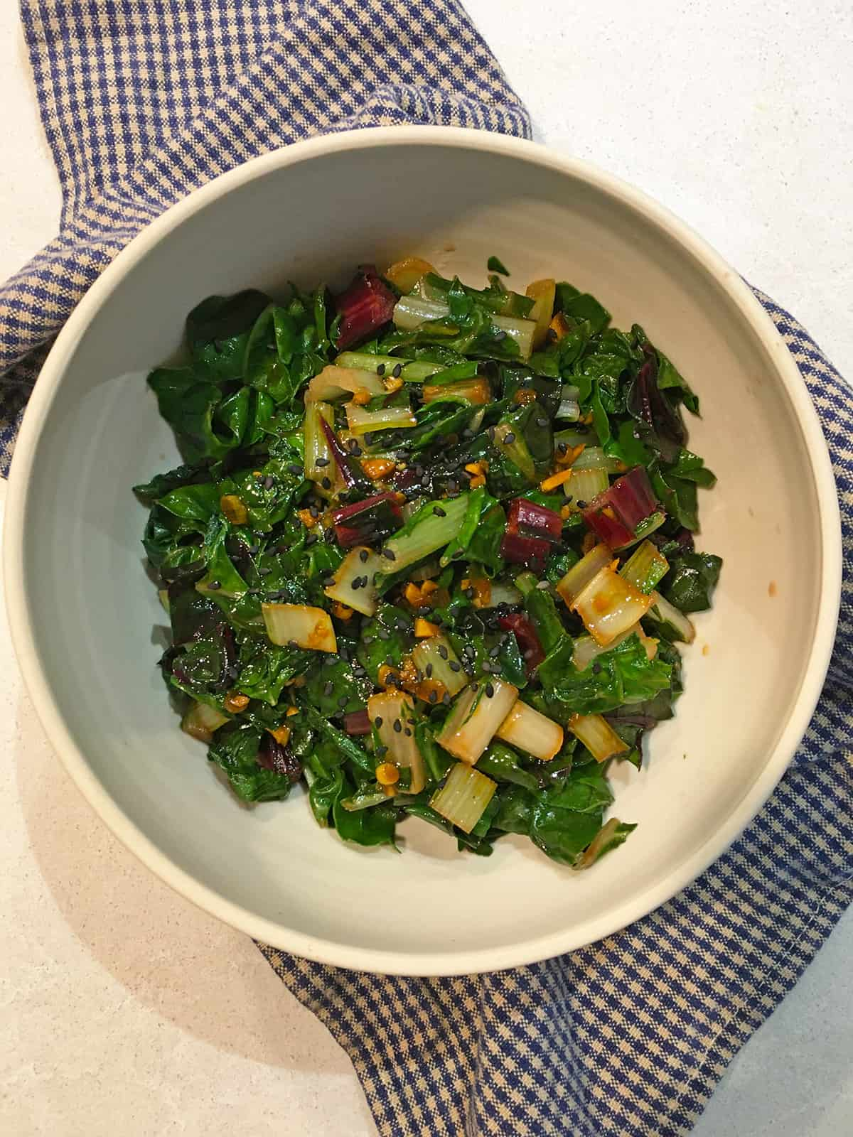 Asian sautéed Swiss chard in a tan ceramic bowl with a blue and tan checkered napkin