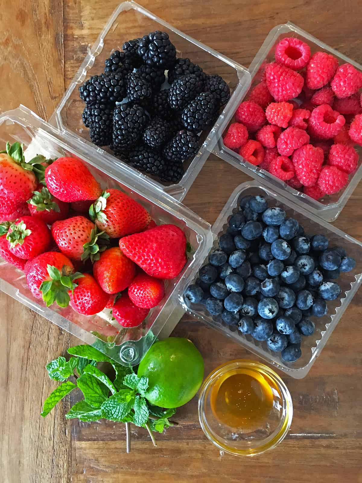 Fresh berry fruit salad ingredients on a brown wood table