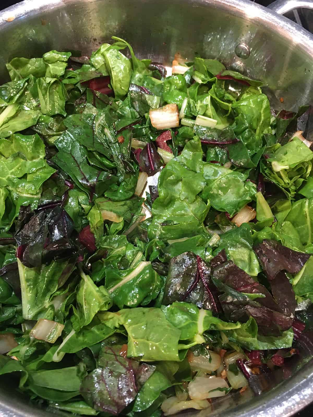 Swiss chard sautéing in a stainless steel skillet