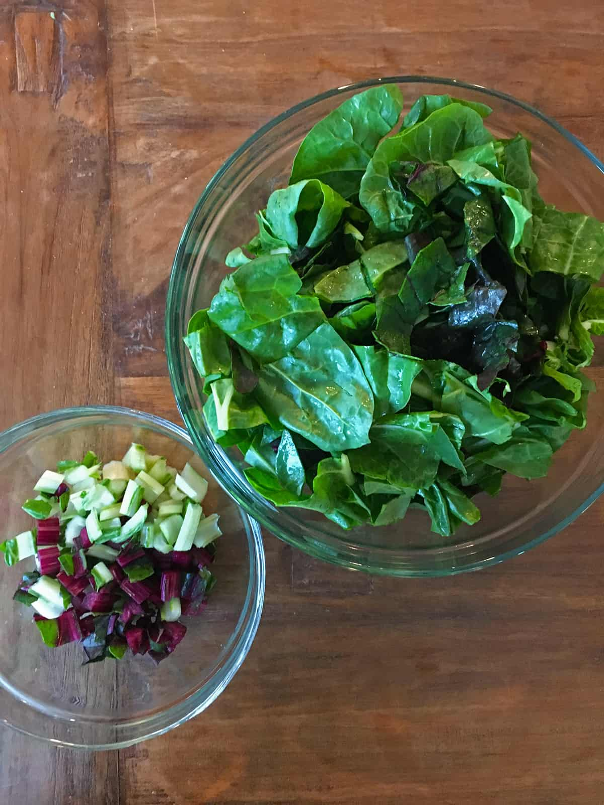 Swiss chard leaves and stems in two glass food prep bowls on a brown wood table